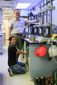 写真2:ピーターと。写真1でwhole roundのIW試料をゲットしたら、すぐ1つ下のChem Lab(写真に写っている実験室)に降りて、そのまま中身を取り出しスクイーザーに入れて、写真の機械で圧力をかけて間隙水を絞り出します。その間、本来ならヘルメットも安全ゴーグルも手袋も付けたままです。これはスタッフサイエンティストのカルロスが時間が空いている時に写真を撮りにきてくれて、二人でいつもやっているポーズをとったものです。
