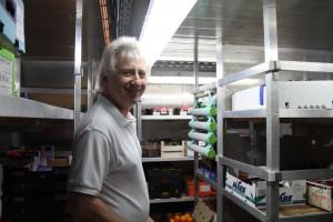 写真3:冷蔵保管庫の説明をしてくれているWallyさん。奥に見える、4本ぶら下がっている灰色の棒がエチレンを吸着する棒。これによって長期間、野菜や果物の新鮮さを保つことが出来る。